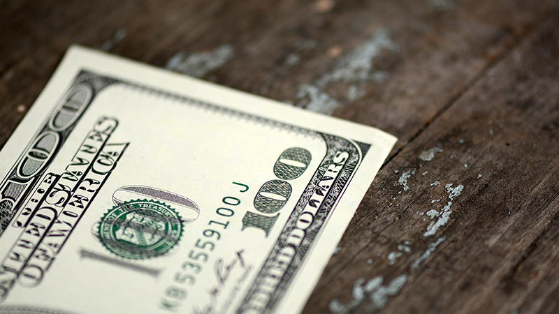 One hundred dollar bill on a wooden table
