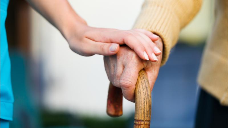 Elderly man with cane walking with nurse