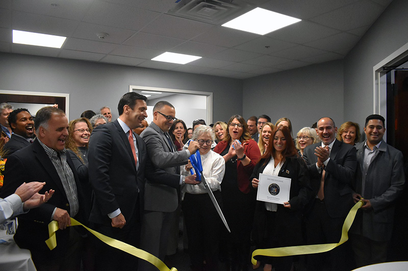 jennifer van tuyl and anthony morando cutting ribbon revealing new office space
