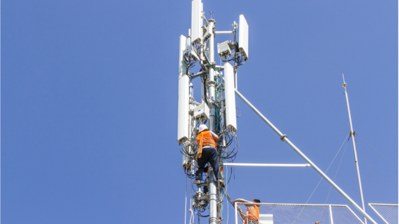 Technician working on communications tower - 5G